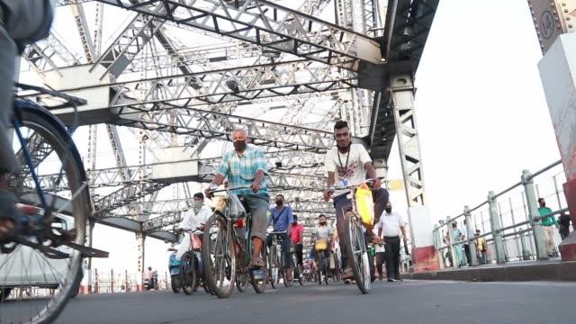commuters ride their bicycles past the landmark howrah bridge over ganga river on world bicycle day on june 3, 2020 in kolkata, india. - howrabron bildbanksvideor och videomaterial från bakom kulisserna