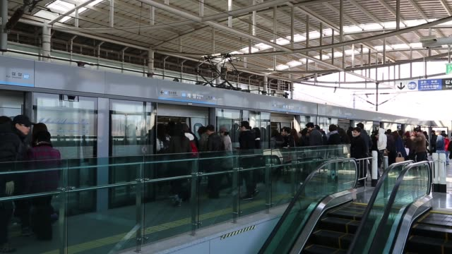 stockvideo's en b-roll-footage met commuters stand on a busy platform at a subway station in incheon as a train arrives commuters ascend escalators to subway station platform subway... - incheon