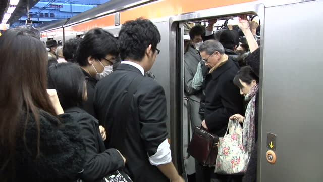 commuters trying to get on the jr shinjuku chuo line platform for a train home - 救助隊点の映像素材/bロール