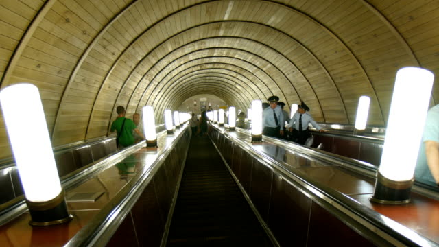 commuters use an escalator in a subway station / moscow, russia - metropolitana video stock e b–roll