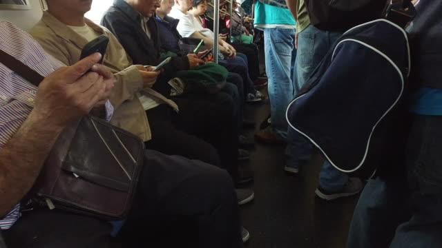Commuters using smart phone on New York subway train