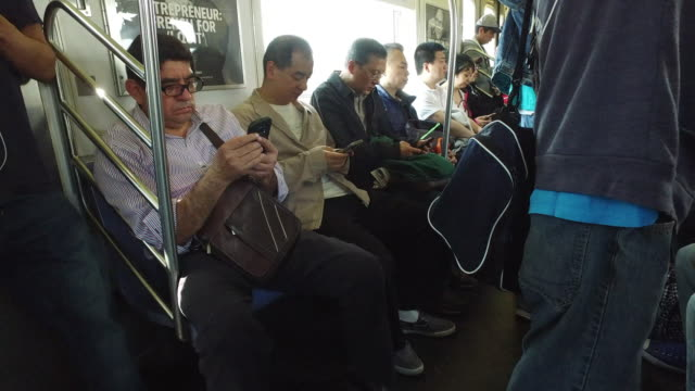 Commuters using smartphone on New York subway train