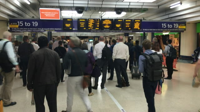 Commuters viewing information boards in a train station whilst industrial action is underway