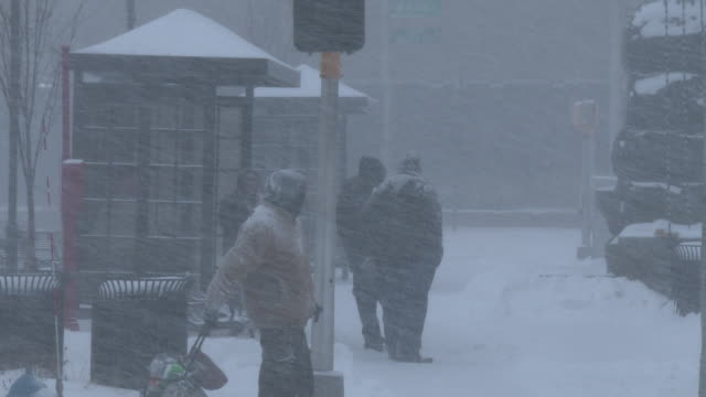 Commuters wait at a bus stop in Waterbury Connecticut as powerful winds and heavy snow create near whiteout conditions during an intense nor'easter