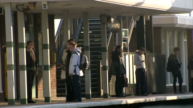 Commuters wait for their train at Polegate railroad station. Available in HD.
