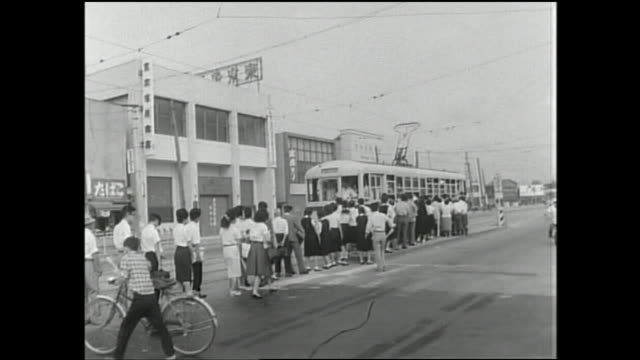 stockvideo's en b-roll-footage met commuters wait in a long line to board the toei streetcar as bicyclists speed past them. - 1961