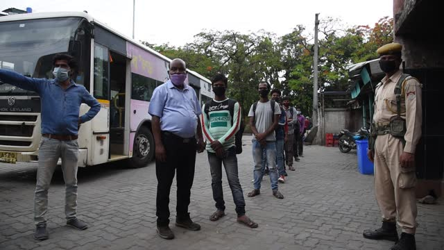 commuters waiting as they are maintaining social distancing in a bus stand for boarding in a bus to reach home, after state authorities eased... - people in a line stock videos & royalty-free footage
