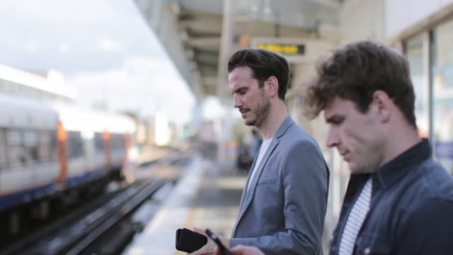 stockvideo's en b-roll-footage met commuters waiting on platform for train to arrive - perron