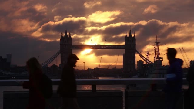 commuters walk across london bridge against a backdrop of tower bridge and the shard during sunrise in london, u.k., on friday, oct. 21, 2016 - 2016 video stock e b–roll