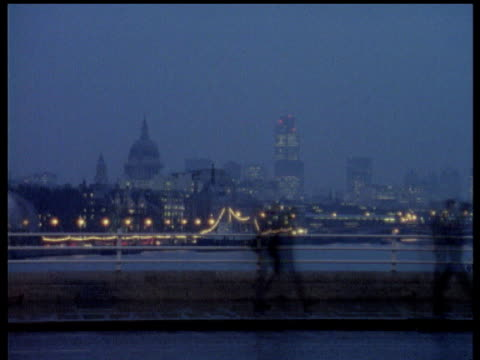 commuters walk across waterloo bridge carrying umbrellas in wet and windy weather with st paul's cathedral in background london - city von london stock-videos und b-roll-filmmaterial