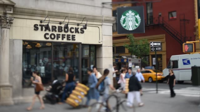 commuters walk by a starbucks coffee shop located on the corner of east 17th street and broadway in union square manhattan ny on the morning of july... - スターバックス点の映像素材/bロール