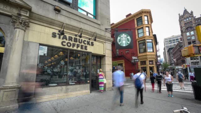 commuters walk by a starbucks coffee shop located on the corner of east 17th street and broadway in union square manhattan ny on the morning of july... - ecke eines objekts stock-videos und b-roll-filmmaterial