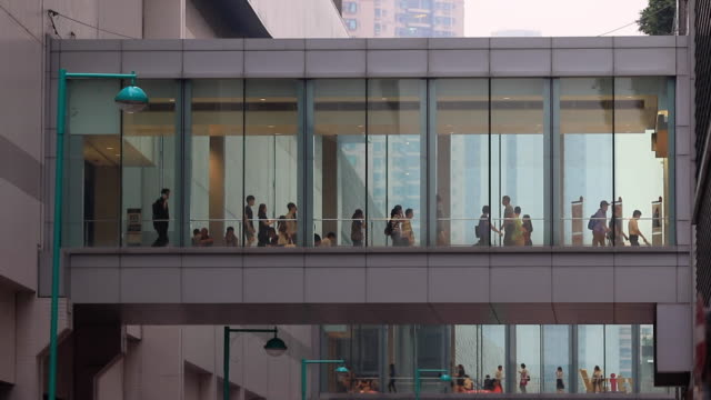 Commuters walk on a indoor footbridge during rush hour in Hong Kong