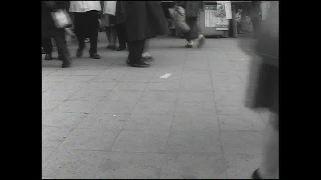 Commuters walk on a sidewalk near Shibuya Station in Tokyo, Japan.