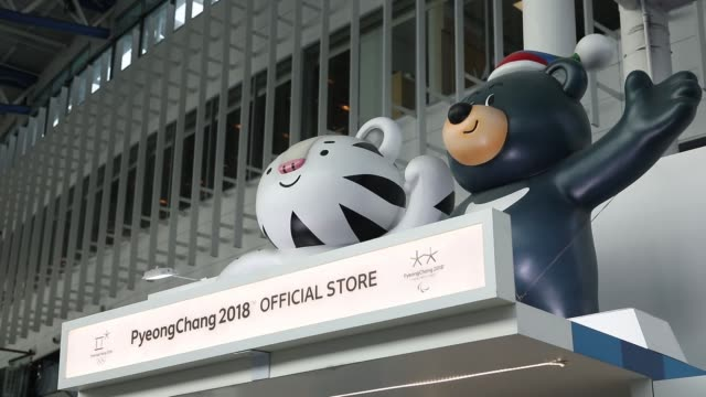 Commuters walk past customers browsing Olympic merchandise at an 2018 PyeongChang Winter Olympic Games official store inside Seoul Station in Seoul...