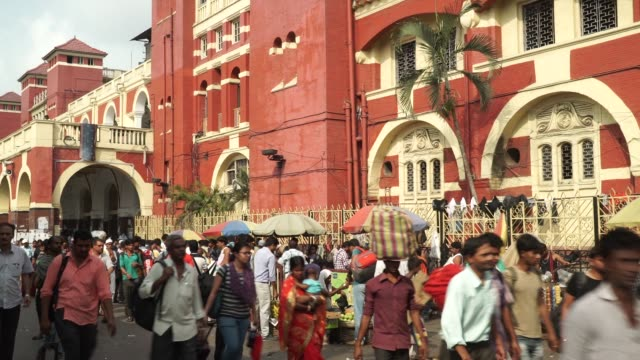 Commuters walk past the Howrah Junction railway station in Kolkata India on Friday May 26 Commuters walk past street vendors outside the Howrah...