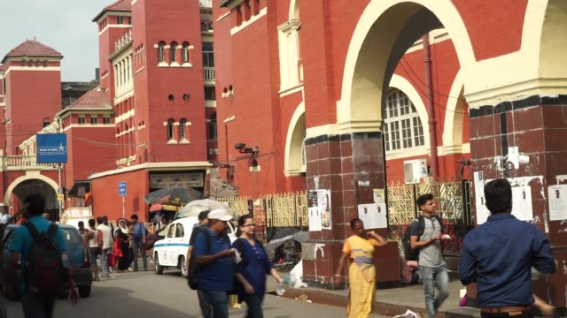 Commuters walk past the Howrah Junction railway station in Kolkata India on Friday May 26 The Howrah Junction railway station stands in Kolkata