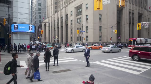 Commuters walk through the financial district as camera pans right in Toronto Ontario Canada on June 24 2017