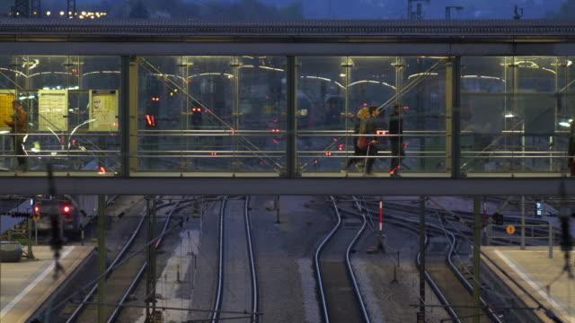 Commuters Walking Across Railway Station Footbridge