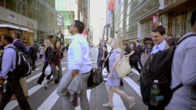 vídeos y material grabado en eventos de stock de commuters walking in city business district. people crossing crowded street in new york - paso de cebra