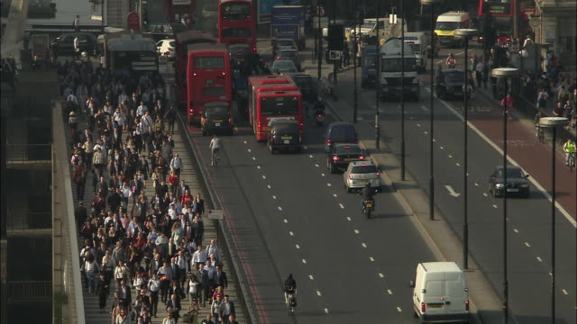 HA WS Commuters walking over London Bridge as cyclists and traffic pass on road/ London, England