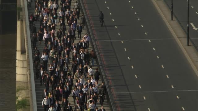 HA WS Commuters walking over London Bridge as traffic passes on road/ London, England