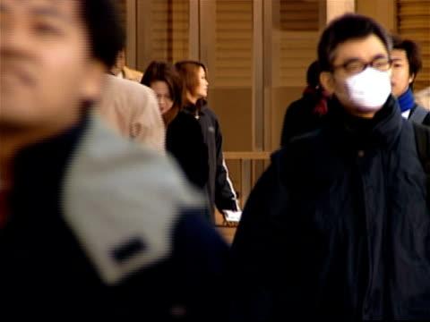 commuters walking through shinjuku station at rush hour / man wearing mask to prevent spread of illness / tokyo, japan - 煙草製品点の映像素材/bロール