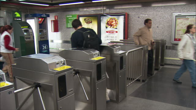 montage commuters walking through turnstiles in subway station, madrid, spain - 2004 stock videos & royalty-free footage