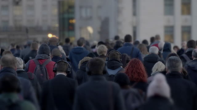 commuters walking to work, slow motion rear view. 60fps. - vita cittadina video stock e b–roll