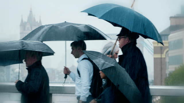 Commuters with umbrellas in the rain. Side view.