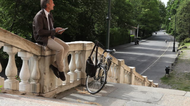 vídeos de stock, filmes e b-roll de commuting businessman uses digital tablet on marble railing - só um adulto de idade mediana