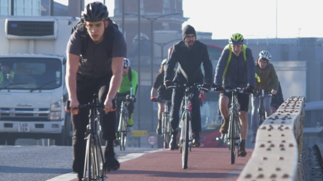 commuting cyclists 4k sidelight. - pendler stock-videos und b-roll-filmmaterial