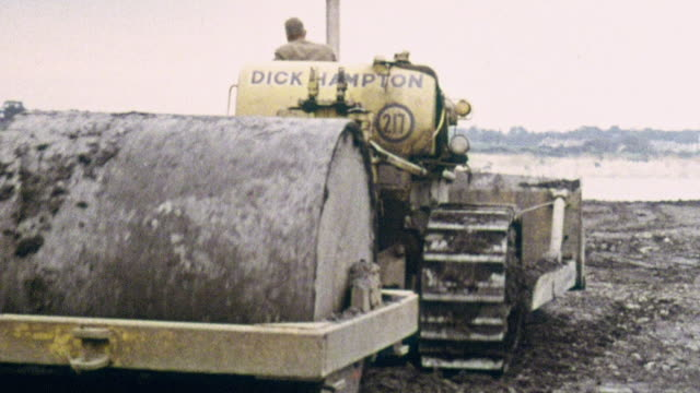 1969 montage compactor packing down black shale material and digger excavating jacking pits in preparation for building the hoverport at pegwell bay / ramsgate, kent, england - ramsgate stock videos & royalty-free footage