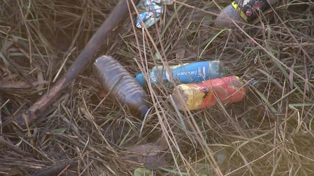 companies commit to making all plastic recyclable by 2025; england: ext tilt up plastic by river bed various shots plastic bottles littered around... - bird stock videos & royalty-free footage