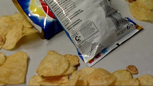 companies to start using labels showing products' carbon emissions; england: london: int walkers crisp packets and crisps scattered on table top... - portionspåse bildbanksvideor och videomaterial från bakom kulisserna