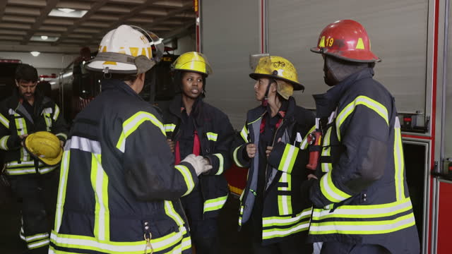 company officer talking to firefighters at engine house - fire station stock videos & royalty-free footage