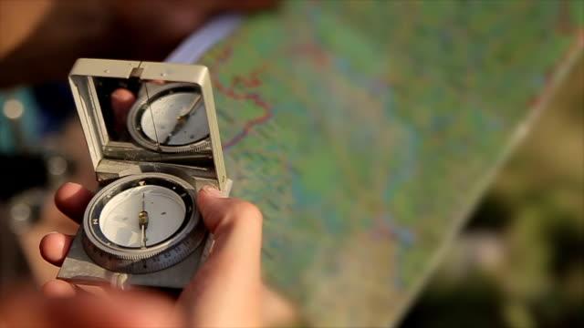 kompass und karte in den händen, nahaufnahme - kompass stock-videos und b-roll-filmmaterial