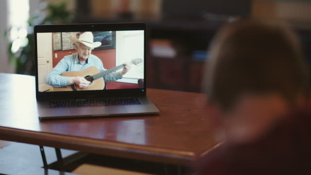 compassionate grandfather teaches his grandson how to play guitar via video call - cowboy hat stock videos & royalty-free footage