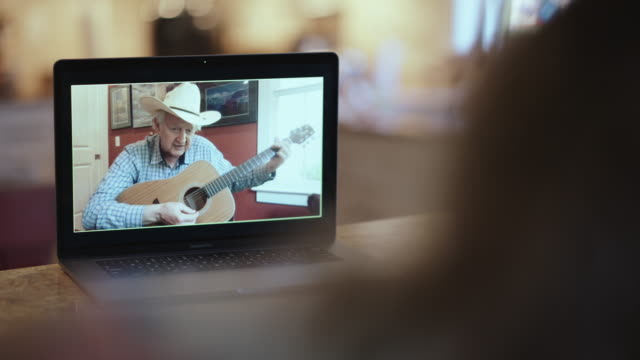 compassionate grandfather teaching how to play the guitar via video call - over the shoulder stock videos & royalty-free footage