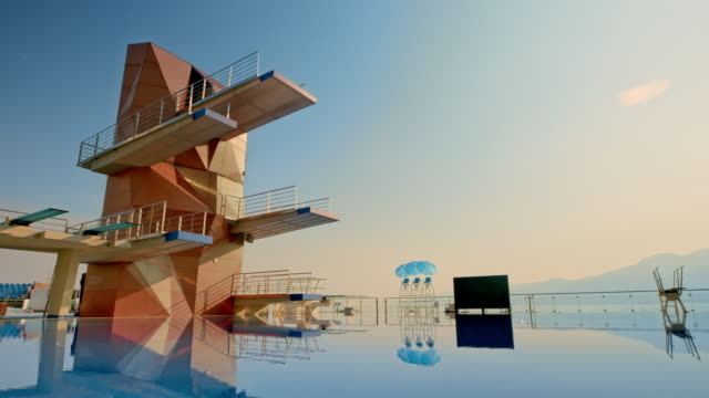 cs competitive diving tower above the tranquil pool at sunset - crane shot stock videos & royalty-free footage