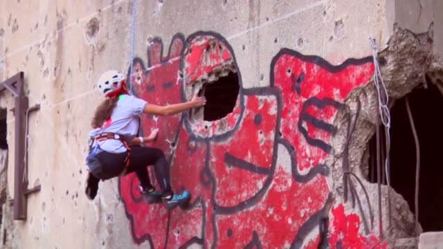 vidéos et rushes de competitors climb the hole-ridden facade of beirut's al-kamal building which was severely damaged during the lebanese civil war during an urban... - facade