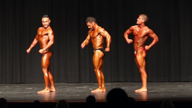 vídeos de stock e filmes b-roll de competitors in the men's under 70kg division pose on stage during the 2014 ifbb victorian bodybuilding championship on october 05 2014 in melbourne... - body building