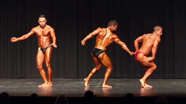 competitors in the men's under 70kg division pose on stage during the 2014 ifbb victorian bodybuilding championship on october 05 2014 in melbourne... - body building stock-videos und b-roll-filmmaterial