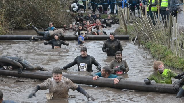 competitors navigate the water tunnel section during the tough guy challenge endurance race on january 27 2013 in telford england every year... - endurance race stock videos and b-roll footage