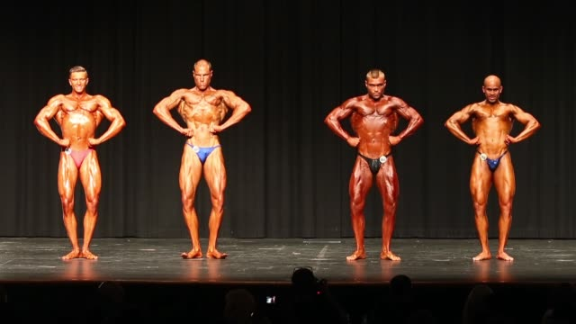 competitors pose on stage during the 2014 ifbb victorian bodybuilding championship on october 05 2014 in melbourne australia - body building stock-videos und b-roll-filmmaterial