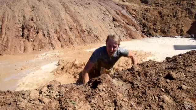 competitors run through mud holes climb under trucks swim across dams and rivers climb up scaffolding move through foam and a number of obstacles as... - mud stock videos & royalty-free footage