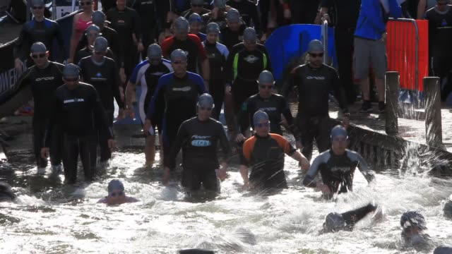 competitors starting the great north swim in lake windermere in the lake district, uk. - sportswear stock videos & royalty-free footage