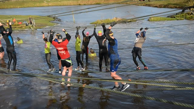 competitors tackle the 'dragon pool' rope section during the tough guy challenge endurance race on january 27 2013 in telford england every year... - endurance race stock videos and b-roll footage