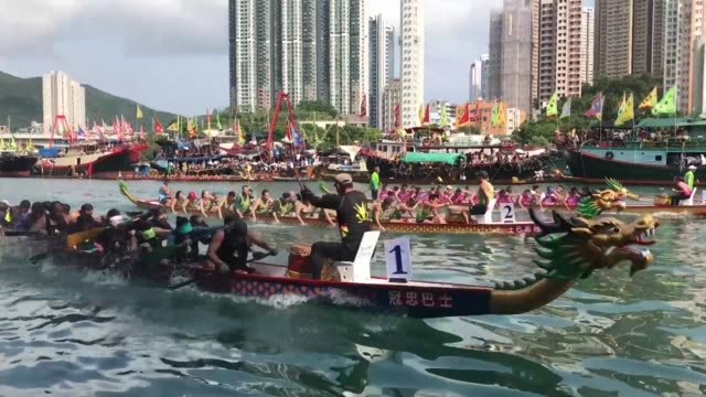 vídeos de stock, filmes e b-roll de competitors take part in the annual dragon boat race to celebrate the tuen ng festival in the aberdeen typhoon shelter in hong kong - ilha de hong kong