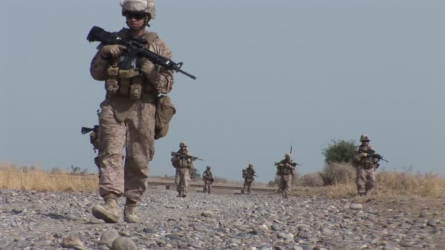 vídeos de stock e filmes b-roll de compilation of footage of us marines on patrol and training afghan police in garmsir district in southern helmand province as well as female us... - helmand